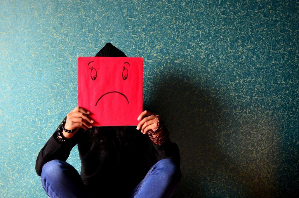 Ein Mensch zeigt seine Depression mit einem Bild vor seinem Gesicht